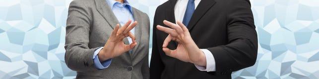 Бизнесмен и коммерсантка показывая одобренный знак Стоковая Фотография