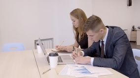 Бизнесмен и коммерсантка работают в со-работая комнате в современном офисе сток-видео
