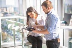 Бизнесмен и коммерсантка работая в интерьере офиса Стоковая Фотография RF