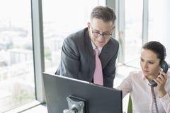 Бизнесмен и коммерсантка работая совместно в офисе Стоковое Фото