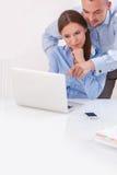 Бизнесмен и коммерсантка работая совместно на компьютере Стоковая Фотография RF