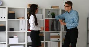 Бизнесмен и коммерсантка связывают стоящий близко шкаф с папками акции видеоматериалы