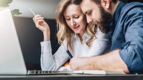 Бизнесмен и коммерсантка сидят на таблице перед компьтер-книжкой, обсуждая концепцию дела Человек пишет ручку стоковое фото