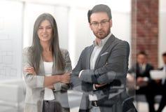 Бизнесмен и коммерсантка смотрят через окно современного офиса стоковое изображение