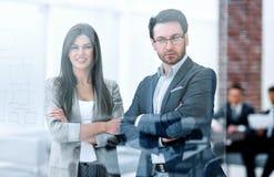 Бизнесмен и коммерсантка смотрят через окно современного офиса стоковая фотография