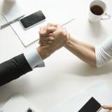 Бизнесмен и коммерсантка состязаясь в армрестлинге Стоковое Изображение