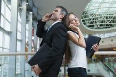 Бизнесмен и коммерсантка спина к спине на мобильных телефонах Стоковая Фотография
