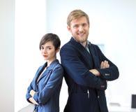 Бизнесмен и коммерсантка стоя спина к спине с пересеченный Стоковая Фотография