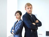 Бизнесмен и коммерсантка стоя спина к спине с пересеченный Стоковое фото RF
