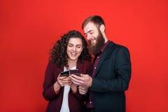 Бизнесмен и коммерсантка с устройствами изолированными на красной предпосылке стоковое фото rf