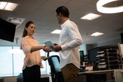 Бизнесмен и коммерсантка трястия руки в офисе Стоковое Изображение