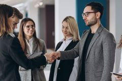 Бизнесмен и коммерсантка тряся руки в конференц-зале стоковые фото