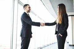 Бизнесмен и коммерсантка тряся руки в офисе с большими панорамными окнами Стоковые Фото