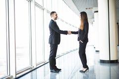 Бизнесмен и коммерсантка тряся руки в офисе с большими панорамными окнами Стоковая Фотография