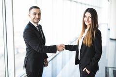 Бизнесмен и коммерсантка тряся руки в офисе с большими панорамными окнами Стоковое Фото