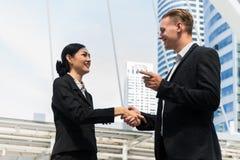 Бизнесмен и коммерсантка тряся руки для демонстрировать их согласование подписать согласование или контракт между их фирмами Стоковые Изображения RF