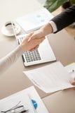 Бизнесмен и коммерсантка тряся руки, подписывая контракт, t Стоковая Фотография RF