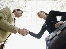 Бизнесмен и коммерсантка тряся руки против потолка Стоковое Изображение RF