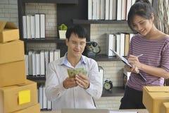 бизнесмен и коммерсантки держа выгоду денег которая получает форму продавая онлайн продукт стоковая фотография rf