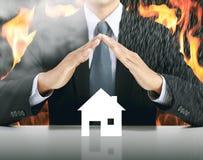 Бизнесмен и дом с предпосылкой огня стоковые изображения