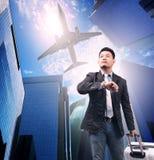 Бизнесмен и принадлежа багаж стоя против городского строения Стоковые Изображения RF