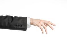 Бизнесмен и тема жеста: человек в черном костюме и белой рубашке показывая жест рукой на изолированной белой предпосылке в studi Стоковые Изображения