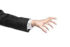 Бизнесмен и тема жеста: человек в черном костюме и белой рубашке показывая жест рукой на изолированной белой предпосылке в studi Стоковое Фото