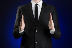 Бизнесмен и тема жеста: человек в черном костюме и белом показе рубашки показывать с руками на синей предпосылке в стержне Стоковое Фото