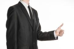 Бизнесмен и тема жеста: человек в черном костюме и связь держа его руку перед им и выставками thumb вверх изолированный на белизн Стоковое фото RF