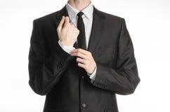 Бизнесмен и тема жеста: человек в черном костюме при пальто связи выправляет его оружия изолированное на белой предпосылке в студ стоковое фото rf