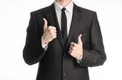 Бизнесмен и тема жеста: человек в черном костюме при связь показывая 2 большого пальца руки рук вверх изолированного на белой пре Стоковое Изображение