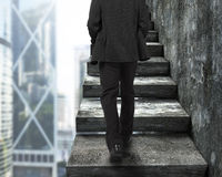Бизнесмен идя вверх по старым конкретным лестницам Стоковое фото RF