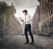 Бизнесмен идя вокруг города стоковое фото