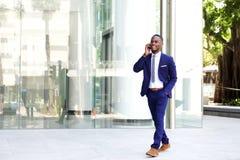 Бизнесмен идя в город используя мобильный телефон Стоковое Фото