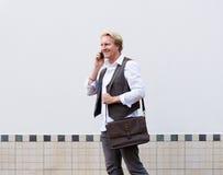 Бизнесмен идя и говоря на мобильном телефоне Стоковое Изображение