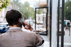 Бизнесмен идя и говоря на сотовом телефоне в городе Стоковое Фото
