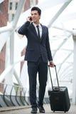 Бизнесмен идя и говоря на телефоне на станции метро Стоковое Фото