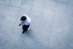 Бизнесмен идя и используя умный телефон Стоковые Фото