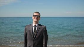 Бизнесмен идя на пляж в костюме, взгляды на камере и улыбки сток-видео