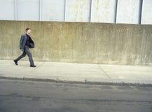 Бизнесмен идя на тротуар Стоковое фото RF