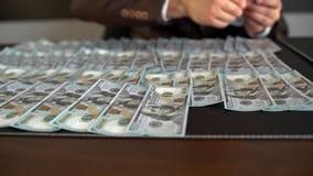 Бизнесмен кладет деньги и доллары на таблицу Мужчина кладет вниз на доллары США таблицы Человек конца-вверх кладет стог  видеоматериал