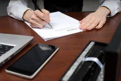 Бизнесмен кладет его подпись на контракт скопируйте космос стоковое фото