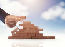 Бизнесмен кладет кирпич для построения стены Концепция новых дела, партнерства, интеграции и запуска стоковое фото