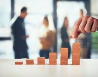Бизнесмен кладет кирпич на кучу кирпичей Концепция растя статистики и успеха стоковое изображение rf