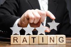 Бизнесмен кладет четвертую звезду над оценкой слова на деревянные блоки Концепция высокой оценки гостиниц и ресторанов стоковое фото