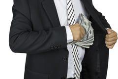 Бизнесмен кладя банкноту 100 долларов в карманн комода на белую предпосылку Стоковое Фото