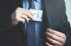 Бизнесмен кладя 100 долларов в его карманн костюма Стоковые Фотографии RF