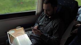 Бизнесмен коммутируя для работы на поезде используя мобильный телефон акции видеоматериалы