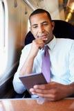 Бизнесмен коммутируя на поезде читая книгу Стоковые Фото