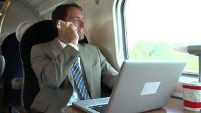 Бизнесмен коммутируя для работы на поезде используя мобильный телефон сток-видео